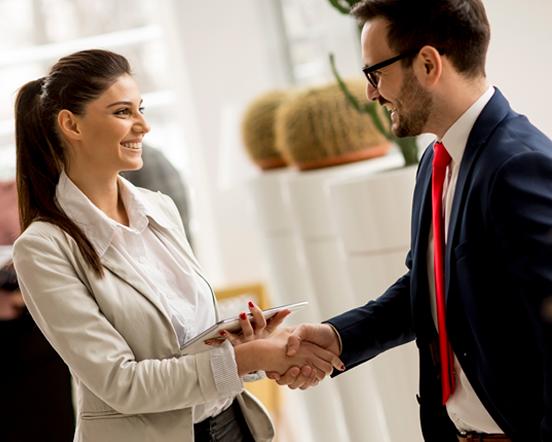 Imagen de una mujer y un hombre estrechando las manos, en señal de que se cerro un negocio.